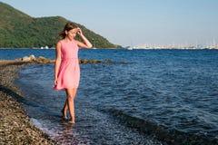 Fille au coucher du soleil marchant le long du bord de la mer Images stock