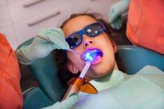 Fille au dentiste obtenant le traitement avec la lumière bleue dentaire photo libre de droits