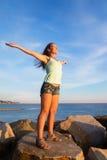 Fille au-dessus de la mer pour rencontrer le coucher de soleil photos stock