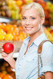 Fille au marché choisissant la pomme de mains de fruits Image stock