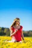 Fille au printemps sur un pré de fleur avec le pissenlit Photo libre de droits