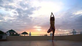 Fille au yoga de pratique de coucher du soleil banque de vidéos