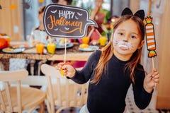 fille aux cheveux foncés de chat assistant à la partie de Halloween tenant les dents gommeuses dans sa bouche images libres de droits
