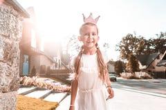Fille aux cheveux foncés gaie de lancement portant peu de sentiment de couronne heureux photos stock