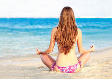 Fille aux cheveux longs dans le bikini dans la pose de lotus en fonction Images stock