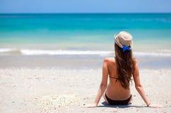 Fille aux cheveux longs dans le bikini et le chapeau de paille en fonction Photographie stock libre de droits