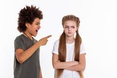 Fille aux cheveux longs fâchée croisant résolument des mains tandis que garçon se dirigeant à elle photos libres de droits