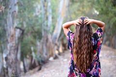 Fille aux cheveux longs regardant en bas du chemin en avant Images libres de droits
