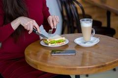 Fille aux coupes de table un sandwich à un déjeuner d'affaires, plan rapproché Photo stock