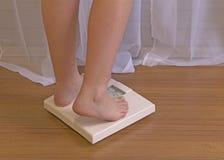Fille aux pieds nus de jeunes énergiques sur l'échelle de salle de bains image stock
