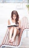 Fille aux pieds nus lisant un livre Photographie stock libre de droits