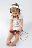 Fille aux pieds nus s'asseyant dans de grands écouteurs Photo stock