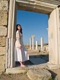 Fille aux pieds nus se penchant des ruines antiques Photographie stock libre de droits