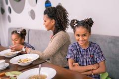 Fille aux yeux noirs mignonne se sentant gaie tout en appréciant le déjeuner de famille photographie stock