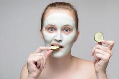 Fille avec de la crème verte sur le visage photos libres de droits