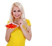 Fille avec de la salade de poivrons, sain blond de consommation de jeune femme d'isolement Photo stock