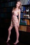 Fille avec de longs cheveux blonds dans la position courte de robe Photo stock
