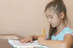 Fille avec de longs cheveux faisant le travail Peu de fille d'école portant des devoirs faisants globaux photo libre de droits