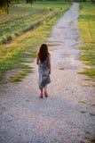 Fille avec de longs cheveux onduleux bruns avec la longue robe élégante dans la couleur anthracite images libres de droits