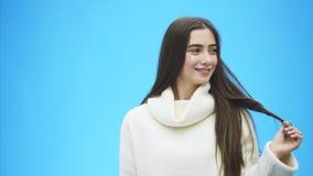 Fille avec de longs cheveux parfaits Une belle femme sur un fond bleu enveloppe des cheveux sur son doigt Brunette Habillé dans a banque de vidéos