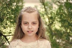 Fille avec de longs cheveux sur le visage calme, fond de nature La fille avec l'offre tresse la coiffure Fille d'enfant avec la c photographie stock libre de droits