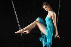 Fille avec de longues pattes dans le siège de robe sur l'oscillation Photographie stock