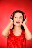 Fille avec des écouteurs Photographie stock