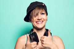 Fille avec des écouteurs et l'attitude positive Femme avec les écouteurs de sourire de musique photos stock