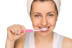 Fille avec des accolades brossant des dents d'isolement Photo libre de droits