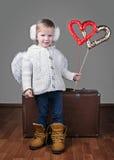 Fille avec des ailes d'anges, des coeurs et la valise de vintage Images stock