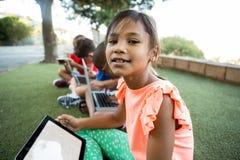 Fille avec des amis à l'aide du comprimé numérique au parc Image stock
