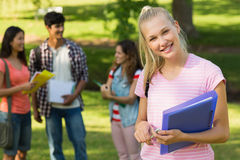 Fille avec des amis d'université à l'arrière-plan au campus Photo libre de droits