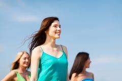 Fille avec des amis marchant sur la plage Images libres de droits
