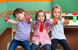 Fille avec des amis montrant les paumes colorées Photographie stock libre de droits