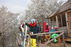 Fille avec des amis passant des vacances en cottage de neige d'hiver Photographie stock