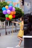 Fille avec des ballons dans la ville photographie stock