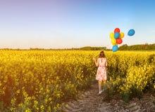 Fille avec des ballons dans le domaine de floraison image stock