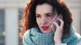 Fille avec des boucles parlant au téléphone sur la rue Elle semble bouleversée au sujet de l'appel clips vidéos