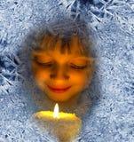 Fille avec des bougies regardant par une fenêtre givrée Photo libre de droits