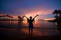 Fille avec des bras grands ouverts au coucher du soleil de plage Photo stock