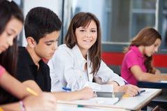 Fille avec des camarades de classe s'asseyant au bureau dans la salle de classe Photo libre de droits