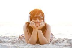 Fille avec des écouteurs au sable de plage. Image libre de droits