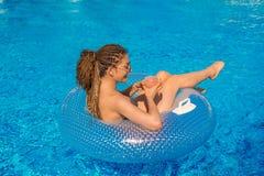 Fille avec des dreadlocks de cornrows de zizi se situant en cercle de natation Photo stock