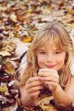 Fille avec des feuilles d'automne Image stock
