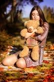Fille avec des feuilles d'un ours en automne photographie stock