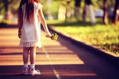 Fille avec des fleurs en parc Photographie stock