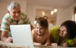 Fille avec des grands-parents à l'aide de l'ordinateur portable image libre de droits