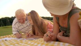 Fille avec des grands-parents, tissu de pique-nique banque de vidéos