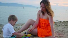 Fille avec des jeux d'enfant avec le sable sur la plage au temps de coucher du soleil banque de vidéos