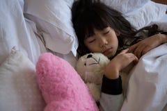 Fille avec des jouets dormant dans la chambre à coucher Photo stock